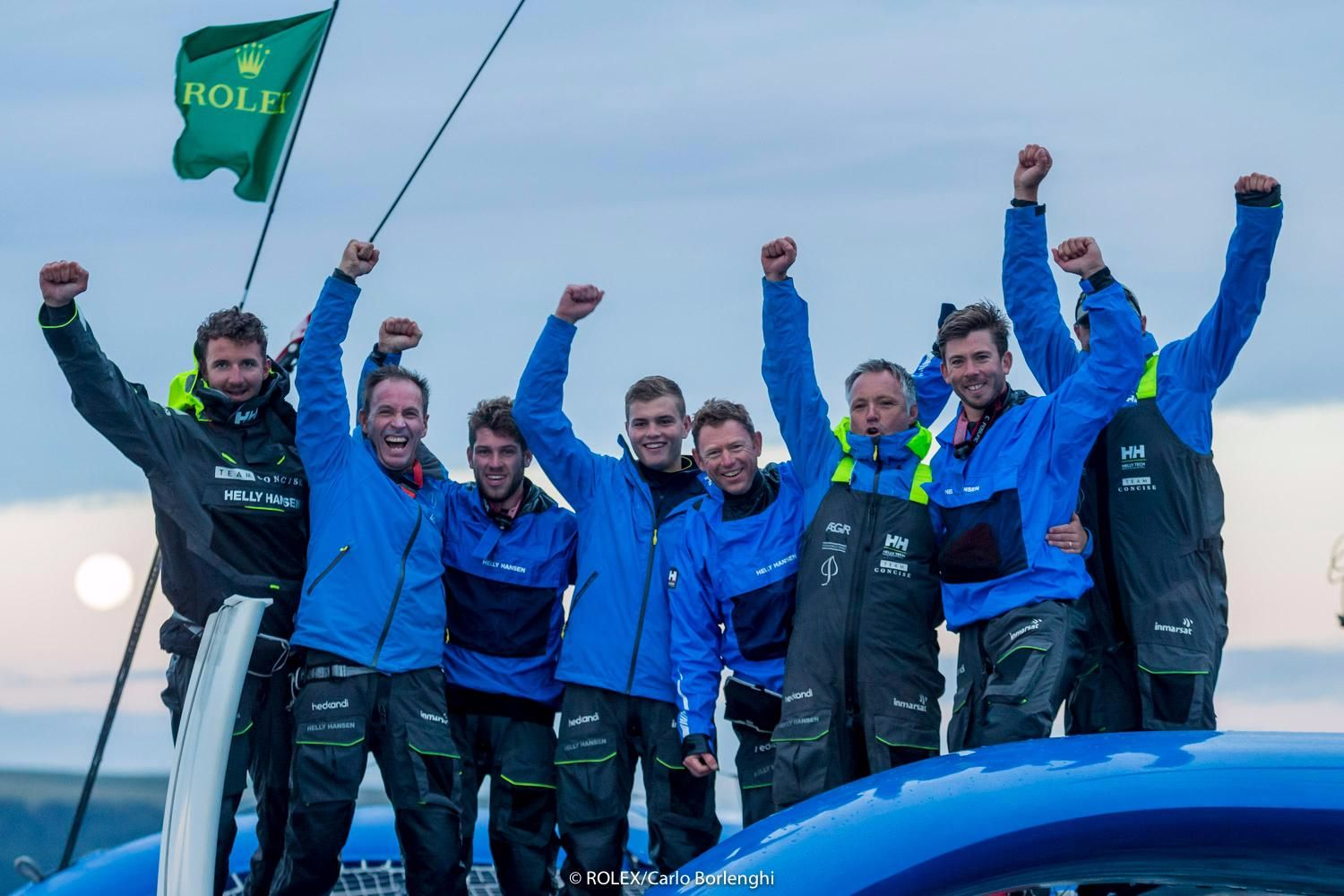 The crew of Concise 10, the MOD70, celebrate at the finish of the Rolex Fastnet Race. Credit: ROLEX/Carlo Borlenghi
