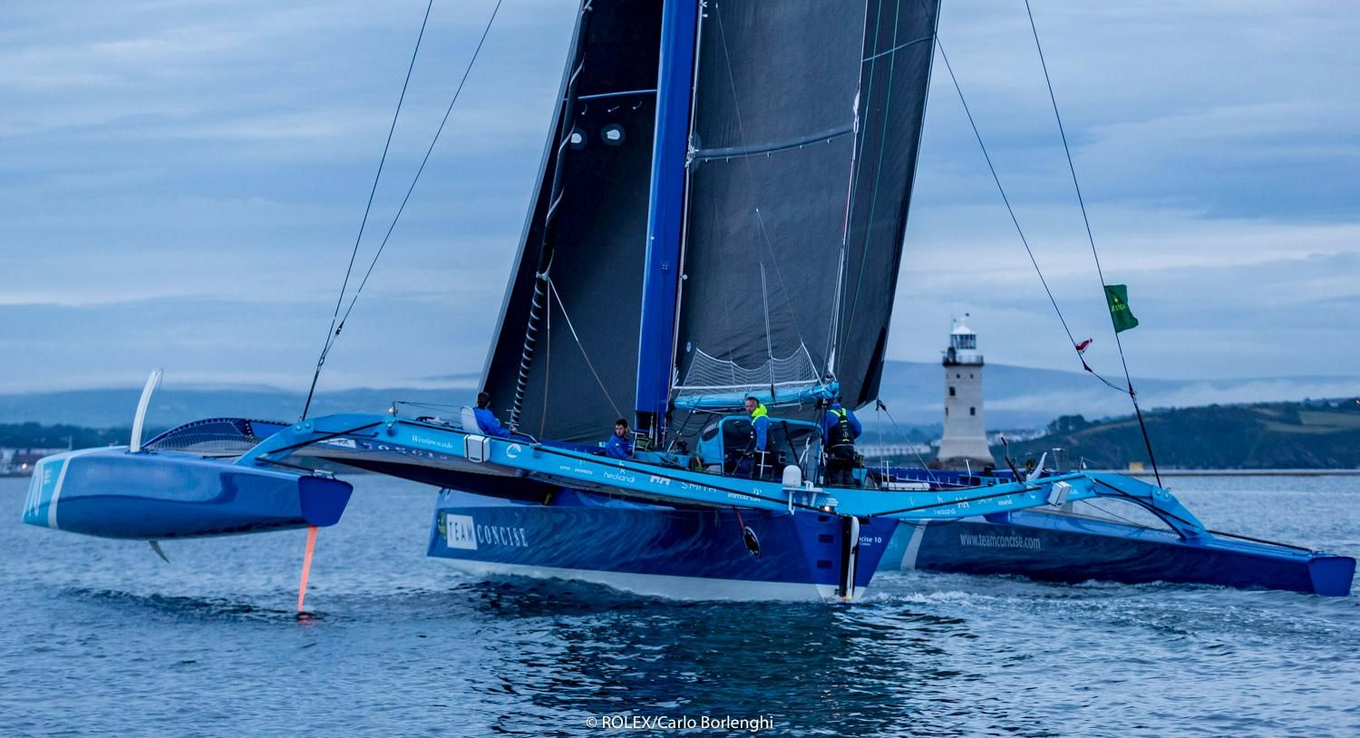 MOD70, Concise 10, cross the finish line of the Rolex Fastnet Race in Plymouth. Credit: ROLEX/Carlo Borlenghi